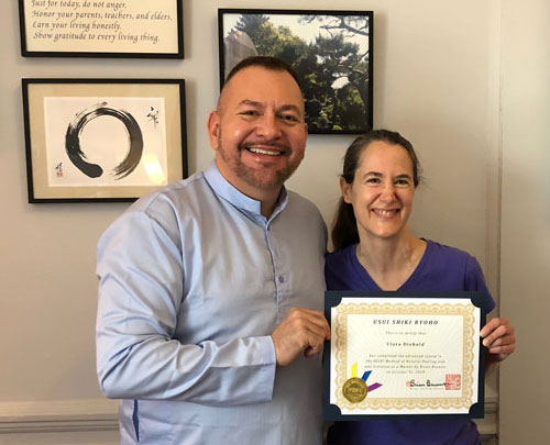 Photo of Clara Diebold receiving her Reiki Master Certificate from Brian Brunius of the NYC Reiki Center