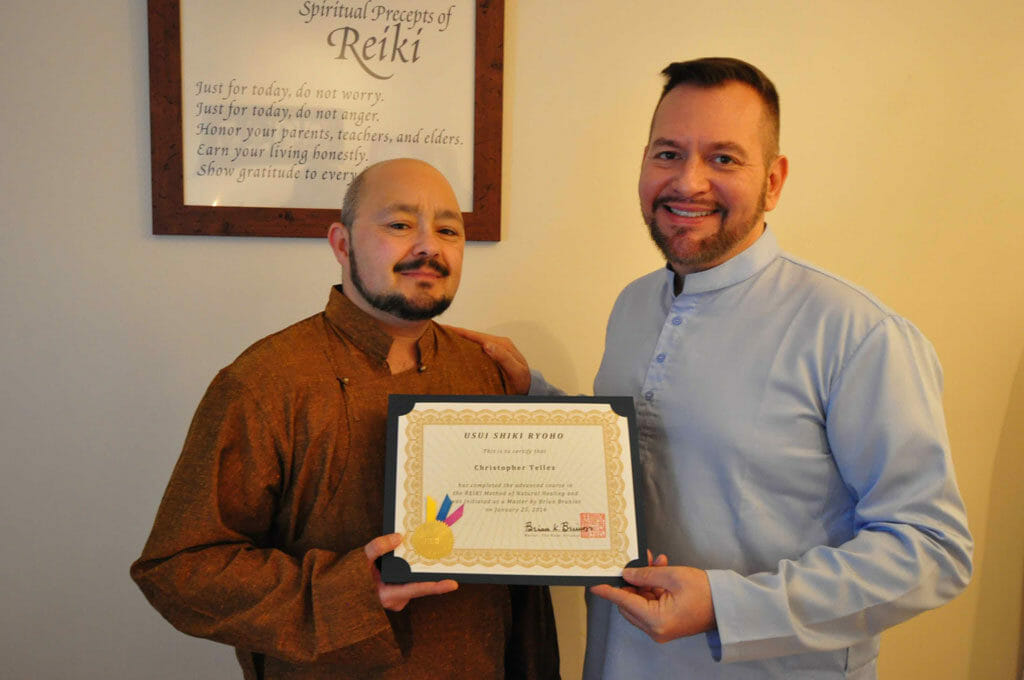 Christopher Tellez of San Francisco California receives his Reiki Master certificate from Brian Brunius of the NYC Reiki Center