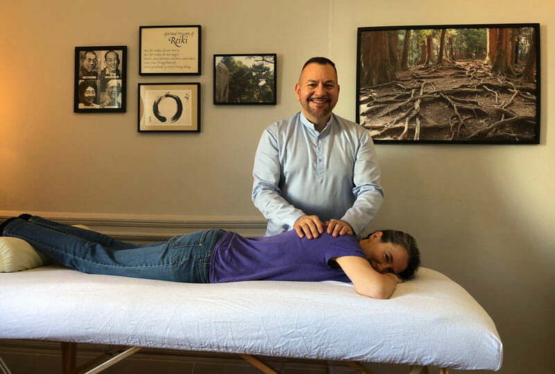 Photo of Clara Diebold receiving a Reiki treatment from her initiating Master Brian Brunius on the day of her Reiki Master initiation