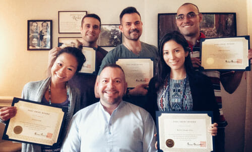 Photo of a Reiki Level 2 class at the NYC Reiki Center with students holding their Reiki Certificates with Master Brian Brunius