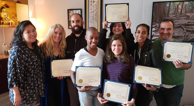 Photo of a Reiki Level 1 class at the NYC Reiki Center with students holding their Reiki Certificates