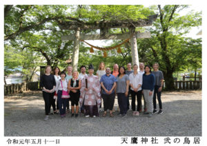 Photo of our tour group at the Taniai Village Shinto temple entry gate donated by Mikao Usui and his brothers in 1925, and with their names inscribed as the donors