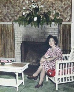 Photo of Hawayo Takata sitting next to a fireplace in 1951